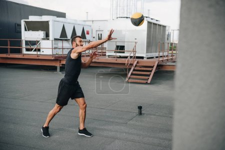 handsome sportsman catching medicine ball on roof