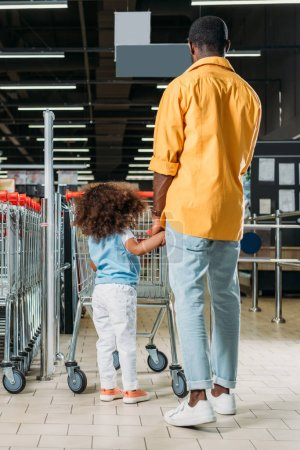 rear view of african american man standing with daughter near shopping trolley in hypermarket