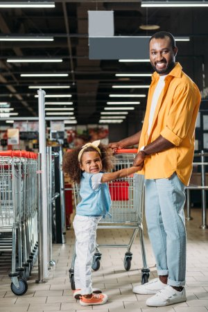 african american man holding hands of daughter near shopping trolley in grocery store