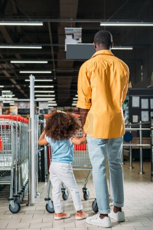 rear view of african american man standing with daughter near shopping trolley in supermarket