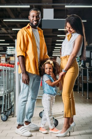 young african american parents with little daughter in grocery store