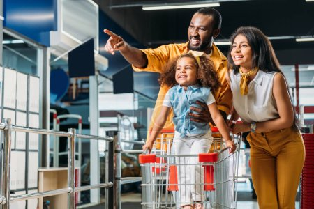 smiling african american man pointing by finger to little daughter and wife in supermarket