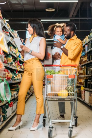 smiling african american man holding daughter while his wife choosing food with shopping list in supermarket