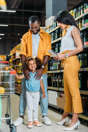 happy african american couple with daughter standing near shopping trolley in supermarket