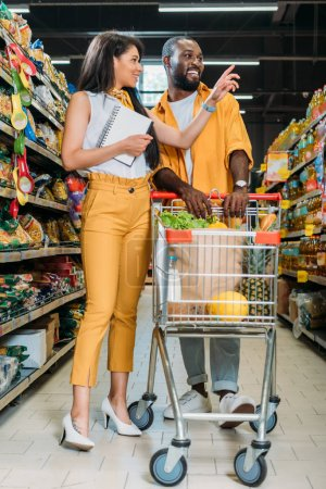 african american woman with shopping list pointing by finger to boyfriend with shopping trolley in supermarket