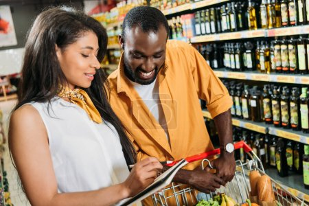 young african american couple with shopping trolley marking shopping list in grocery store