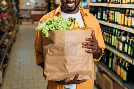 cropped image of african american man holding paper bag with food in grocery store