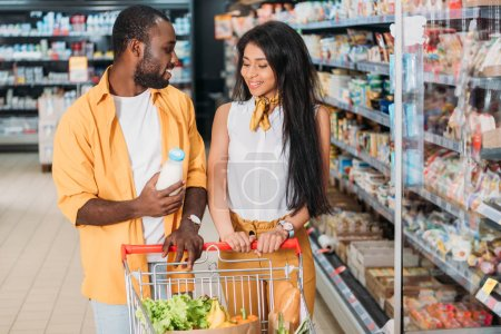 young african american man showing milk to girlfriend with shopping trolley in supermarket