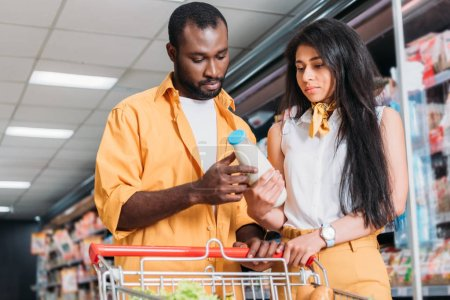 young african american couple with shopping trolley choosing milk in grocery store
