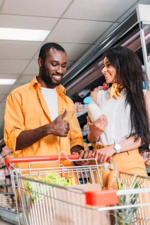 smiling african american man showing thumb up gesture to girlfriend with milk in supermarket