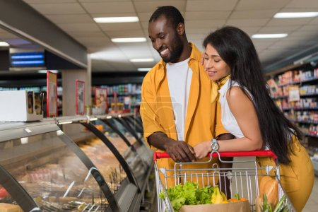 smiling african american couple with shopping trolley choosing food in supermarket