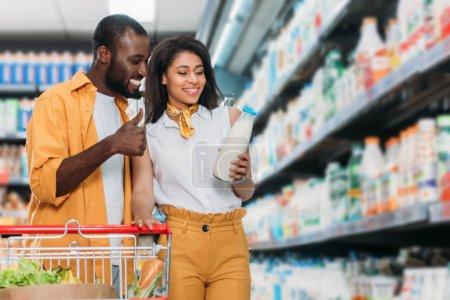 Photo pour Souriant afro-américain fait pouce vers le haut de geste pour petite amie maintenant lait en supermarché - image libre de droit