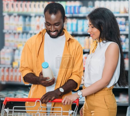 young african american couple with shopping trolley choosing milk in supermarket