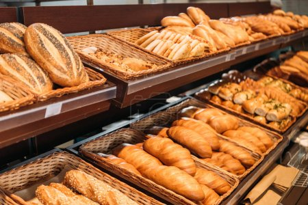Photo for Selective focus of freshly baked various bread in pastry department of supermarket - Royalty Free Image