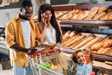 Photo pour Femme afro-américaine parler sur smartphone alors que son mari et sa fille debout près avec chariot de supermarché - image libre de droit