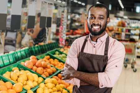 african american male shop assistant in apron standing with crossed arms near fruit department in hypermarket