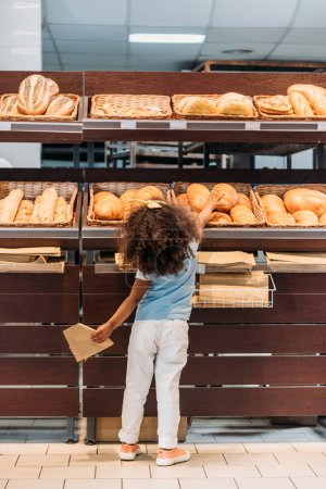 rear view of little child choosing bread in grocery store