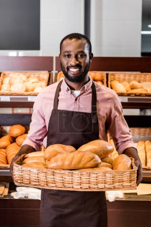 Photo for Smiling african american male shop assistant in apron holding with loaves of bread in supermarket - Royalty Free Image