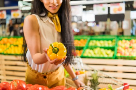 cropped image of african american customer taking bell pepper in supermarket