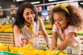 selective focus of african american mother and daughter choosing bell peppers in supermarket
