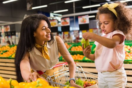 african american woman with child holding bell pepper in grocery store