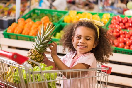 smiling african american kid sitting in shopping trolley with pineapple in grocery store