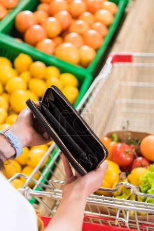 cropped image of woman showing empty purse near shopping trolley in supermarket