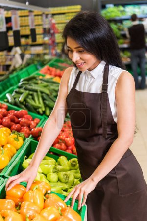 smiling african american female shop assistant in apron arranging bell peppers in supermarket