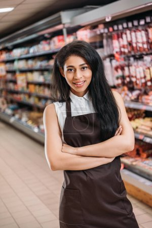 smiling african american female shop assistant in apron with crossed arms looking at camera in supermarket