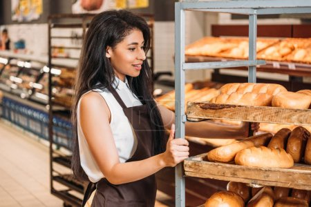 smiling african american female shop assistant in apron arranging fresh pastry in grocery store