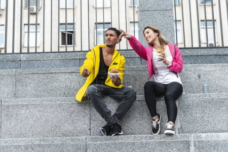 attractive asian woman with burger in hand pointing by finger to mixed race boyfriend at city street