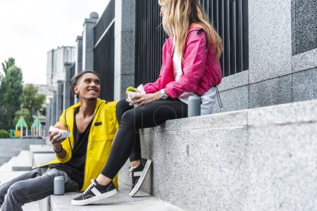 selective focus of smiling couple eating burgers and sitting near soda drinks at city street