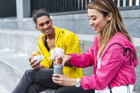 smiling asian woman opening soda drink while her boyfriend holding burgers at urban street