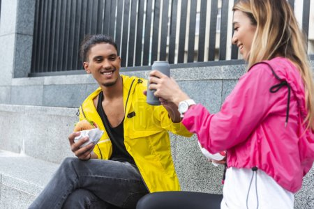 happy multicultural couple with burgers clinking by soda drinks at city street