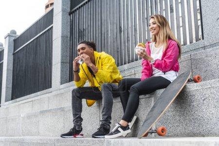 young multicultural couple of skateboarders eating burgers at city street