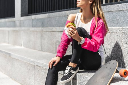 cropped image of young woman sitting with burger near skateboard at city street