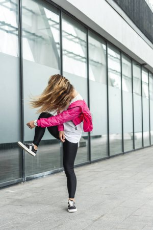 young stylish woman with obscured face by hair dancing at urban street