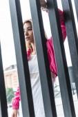 """Постер, картина, фотообои """"низким углом зрения привлекательный стильный азиатские женщины, стоя возле металлический забор на городской улице"""""""