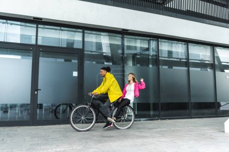 Photo for Happy multicultural couple riding on bicycle at city street - Royalty Free Image
