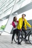 """Постер, картина, фотообои """"Янг, улыбаясь многокультурного пара, сидя на велосипеде на улице города"""""""
