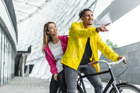 smiling mixed race man sitting on bicycle and pointing by finger to girlfriend at city street