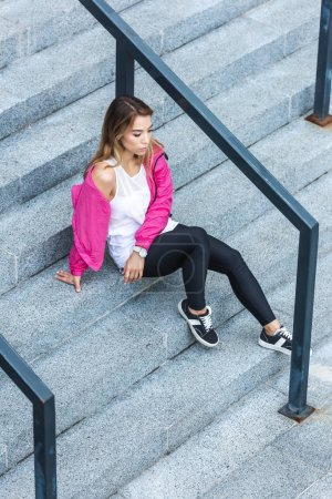 high angle view of young asian woman sitting on stairs at urban street