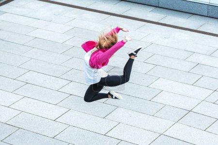 Photo pour Vue grand angle de danseuse urbaine élégante sautant dans la rue de la ville - image libre de droit