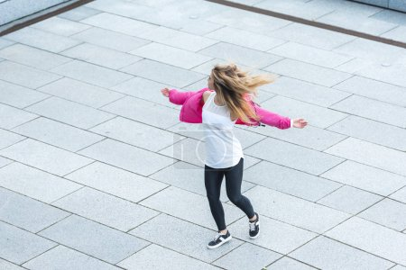 high angle view of young stylish female urban dancer dancing at city street