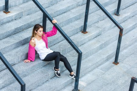 high angle view of stylish asian woman sitting on stairs at urban street