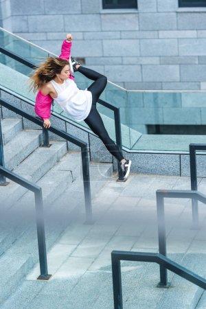 Photo pour Vue grand angle de jeune asiatique élégant femme danseuse urbaine sautant à la ville rue - image libre de droit