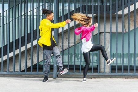 Photo pour Jeune couple multiethnique élégant danser dans la rue de la ville - image libre de droit