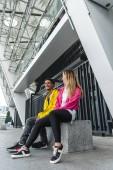 """Постер, картина, фотообои """"Счастливая пара молодых многоэтнического, сидя на городской улице"""""""