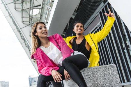 souriante jeune couple multiethnique s'amuser au milieu urbain de la rue