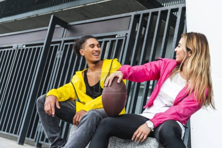 Photo for Young smiling multicultural couple sitting rugby ball at urban city - Royalty Free Image